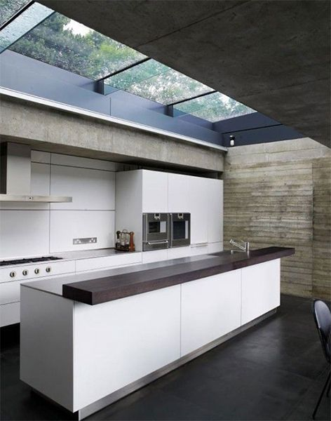 long clear glass on the kitchen's ceiling, black marble floor, dark ceiling, stone wall, white cabinet, white island with dark wooden top