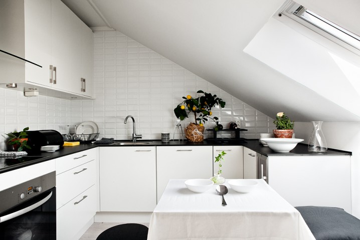 low kitchen, white wall tiles, white kitchen cabinet, black top, white table, black chair