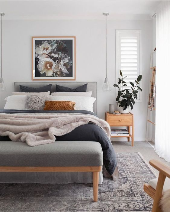 master bedroom, grey wooden floor, detailed rug, white ceiling and wall, grey bench, grey headboard, low clear pendant, wooden side table