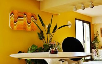 open dining room, white round rug, grey floor tiles, yellow wall white ceiling, white tulip table, yellow stools