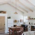 Open Kitchen, Grey Floor, Vaulted White Ceiling, Wooden Beams, White Wall, White Kitchen Top, Brown Rug, Brown Wooden Dining Set