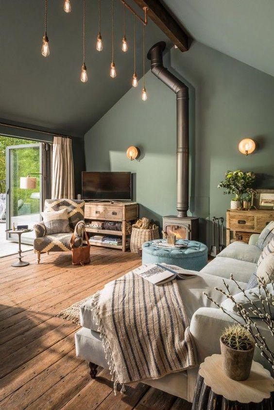 open living room, wooden floor, green wall, green ceiling, small glass pendants, white sofa, wooden cabinet, golden pendant, chair, blue ottoman
