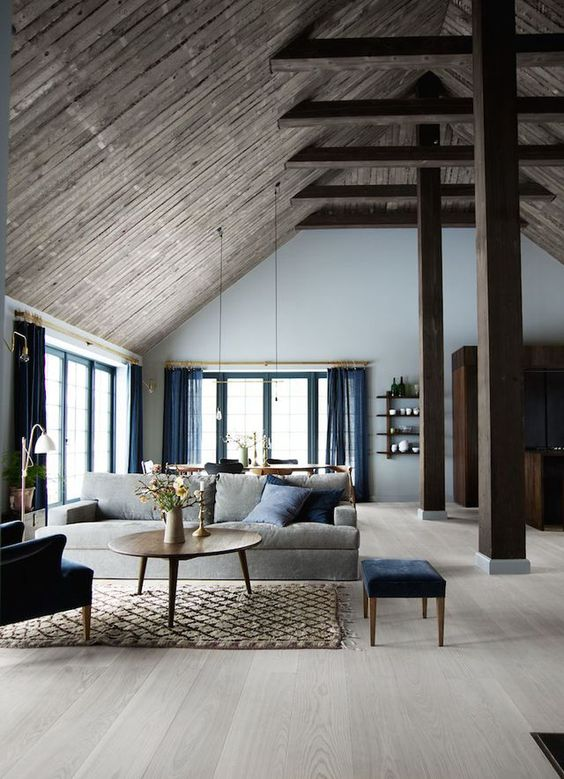 open room, wooden floor, wooden ceiling, wooden posts and beams, rattan rug, grey sofa, blue curtain, round coffee table,