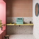 Orange Vertical Lines, Terazzo Wall, Terazzo Floor, Yellow Floating Vanity, Green Sink, Blue Round Mirror, Pink Accent Wall