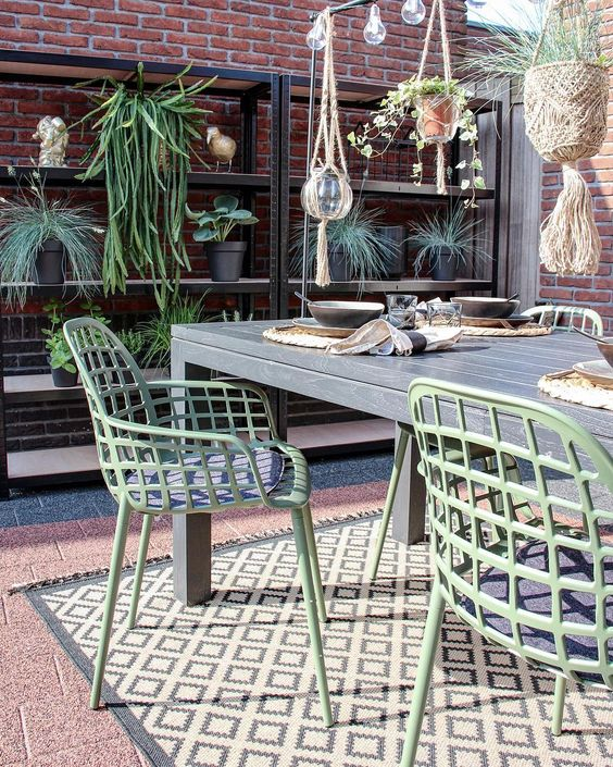 patio, brown floor tiles, open brick, wooden table, green chairs, rattan hanging pots