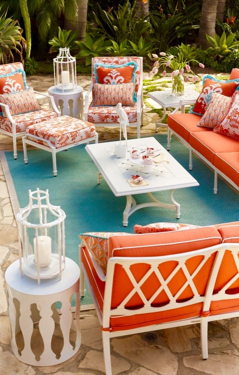 patio, stone floor, white sofa and chair with orange cushion, patterned pillows, white coffee table, blue rug, white side table