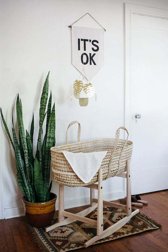 rattan basket crib with wooden rocking support, white wall, wooden floor