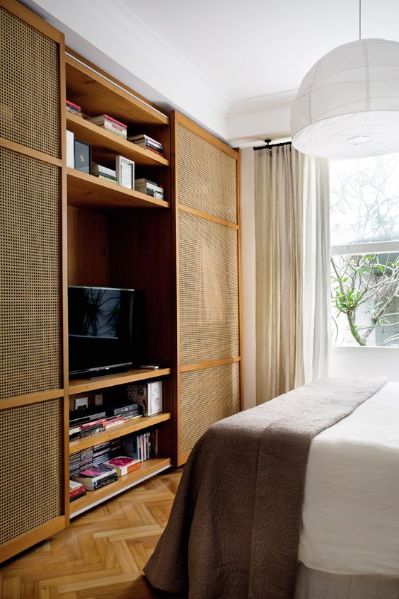 rattan doors on entertainment cabinet, wooden herringbone floor, white ceiling, white bedding, white pendant