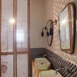 Rattan Grid Doors On The Bathroom, Black Dots Backsplash, Wooden Cabinet, White Sink, White Wall, Mirror
