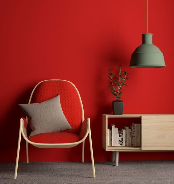 red wall, grey floor, red chair, wooden shelves, grey pendant