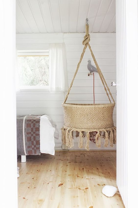 round rattan baby box hung from the ceiling, white plank wall and ceiling, wooden floor, white curtain