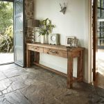 Rustic Console Table With Drawers Black Door Brick Wall White Wall Textured Floor Tile Clock Flowers Vase Wallart Table Lamp Frames