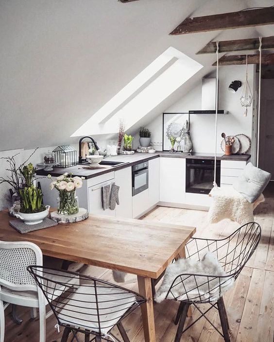 small kitchen, white cabinet, black top, wooden floor, wooden dining table, wird chairs, white chair, swing
