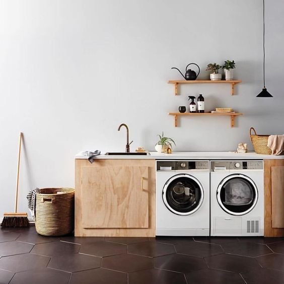 small kitchen with wooden bottom cabinet, laundry machines under the white kitchen top, wooden floating shelves, white wall, black hexagonal tiles