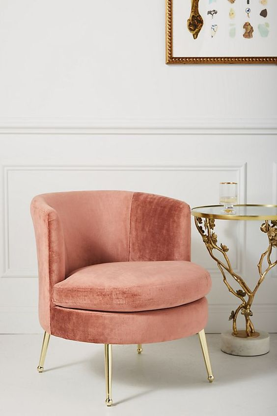 soft pink velvet round chair, gold support legs, white seamless floor, white wall, golden side table with glass top