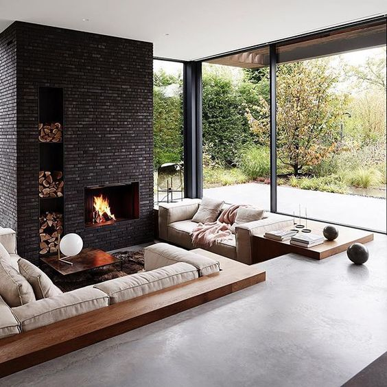 sunken living room, seamless gray floor, glass window, beige sofa, wooden rim, black stone fireplace