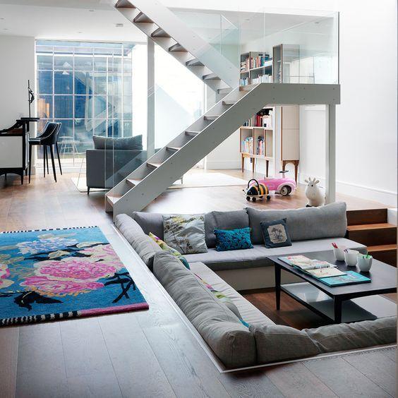 sunken living room, wooden floor, grey sofa, black coffee table, stairs, bookshelves, grey chair, bar, stool, flowery rug