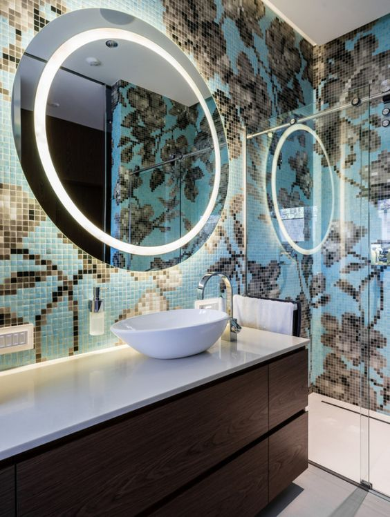 tiny tiles with flowery pattern and blue background, white floor, brown wooden floating vanity, white top, white round sink, round mirror