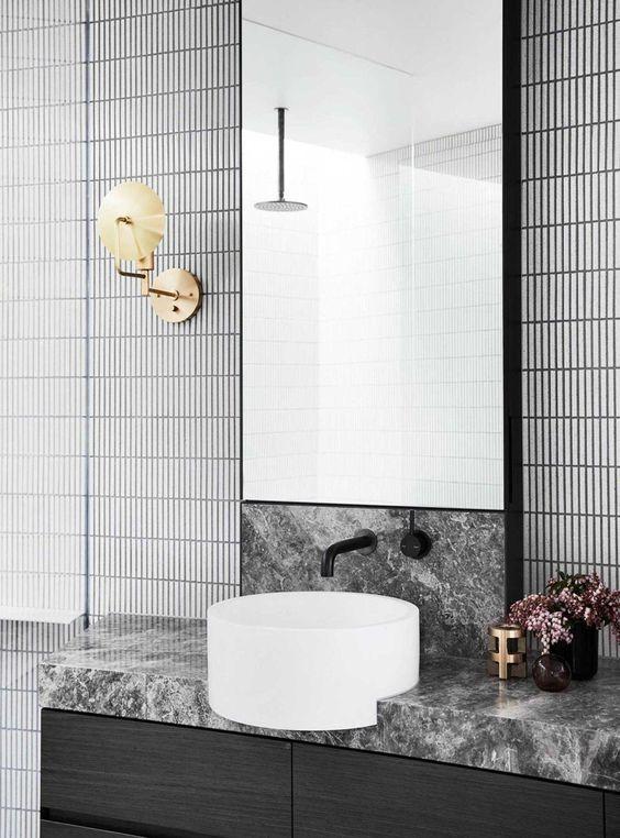 tiny vertical backsplash tiles, black marble vanity, white round sink, irror, black wooden cabinet