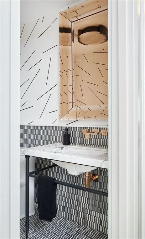 tiny vertical backsplash tiles, white upper wall, tinted mirror, white table sink, black metal table, white toilet