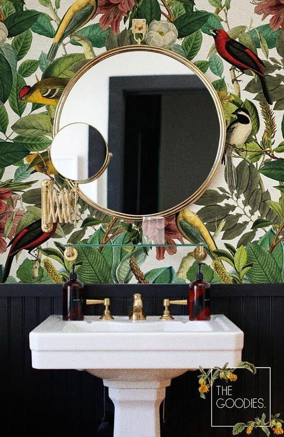 vanity, black wainscoting, patterned upper wall, white sink, round mirror with golden frame