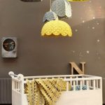 White Crib With Holder And Wheels, Brown Wall, Black Floor, Grey Yellow Crochet Hanging Toys