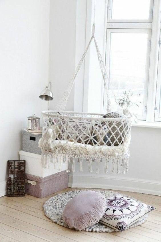 white macrame bed swing, light wooden floor, white wall, round rug, pillows