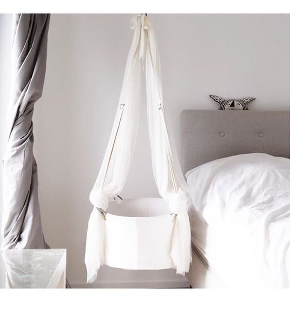 white round bed swing hang from the ceiling, white wall, white bedding, grey headboard, grey curtain