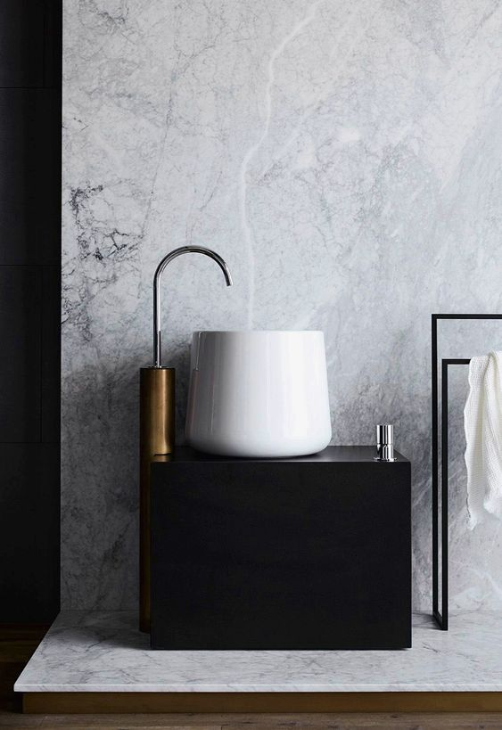 white round small sink, black vanity, copper faucet, white marble