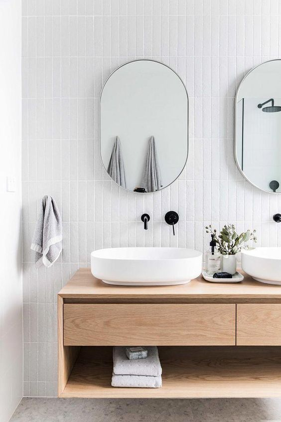 white vertical long tiles on the backsplash, wooden floating vanity with drawer and shelves, white sink, mirror, black faucet