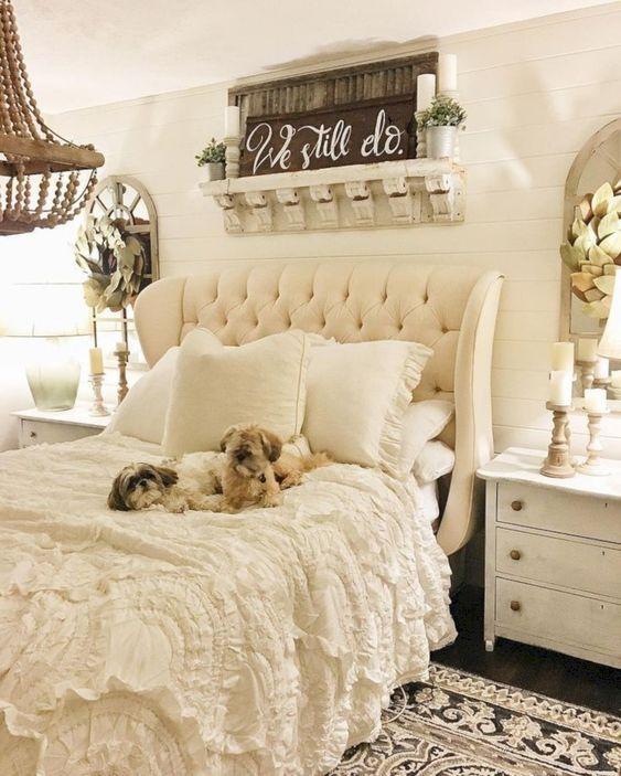 whiteshabby bedroom, white wooden plank, dark wooden floor, rug, white tufted headboard, white bedding, white side table, mirror, white wall decor