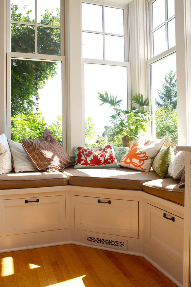window seat in the corner, white storage, wooden floor, colorful pillows