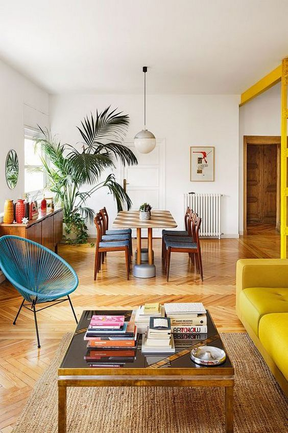 yellow sofa, woden floor, white wall, blue rattan chair, rattan rug, wooden coffee table, open dining set, wooden cabinet