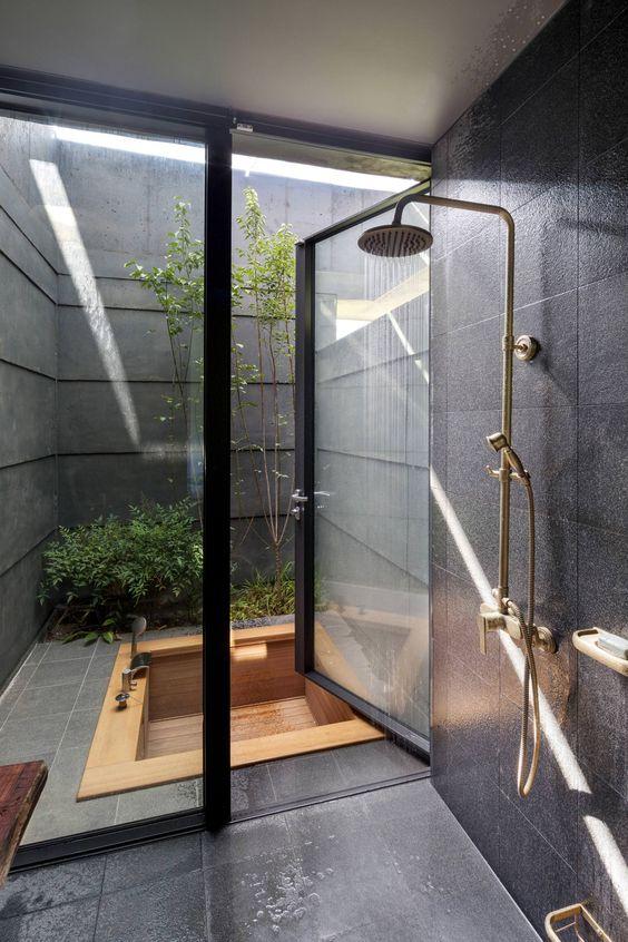 bathroom, black floor tiles, black wall tiles, wooden patterned sunken tub outside, golden shower, glass door