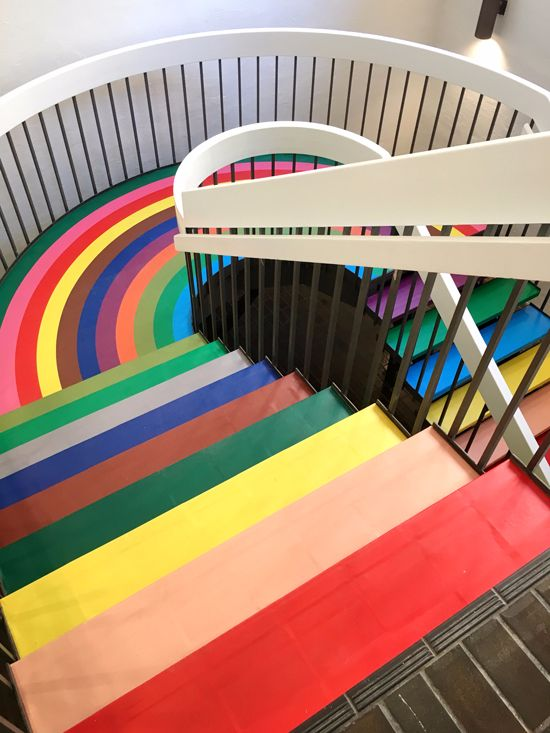 colorful stairs on the top part, white rail, dark brown fence, colorful rainbow floor