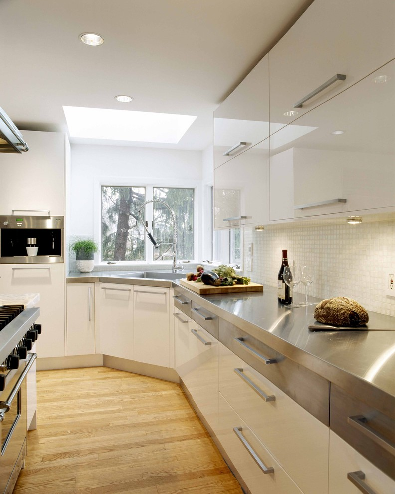 corner kitchen sink cabinet glass windows skylight white gloss kitchen cabinets gray countertop white mosaic backsplash pull out faucet stovetop wooden floor oven