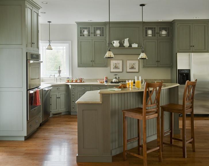 corner kitchen sink cabinet green cabinets island wooden barstools wooden floor windows ovens pendant lamps white walls refrigerator stovetop dishwasher