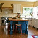 Corner Kitchen Sink Cabinet Textured Backsplash Tiles Blue Island Windows Tan Walls Tan Cabinets Wood Top Red Stools Wooden Floor Stove Range Hood Rug
