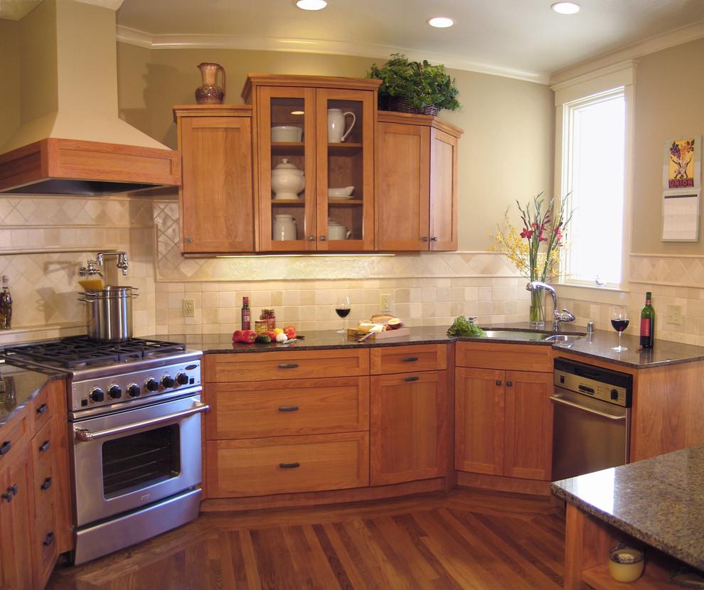 corner kitchen sink cabinet wooden floor wooden cabinets rangehood stove oven dishwasher window beige backsplash glass cabinet door gray granite countertop