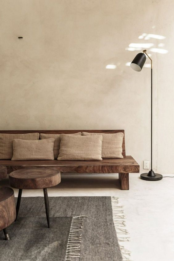 cream wall, seamless floor, wooden bench sofa with pillows, wooden coffee tables, black floor lamp