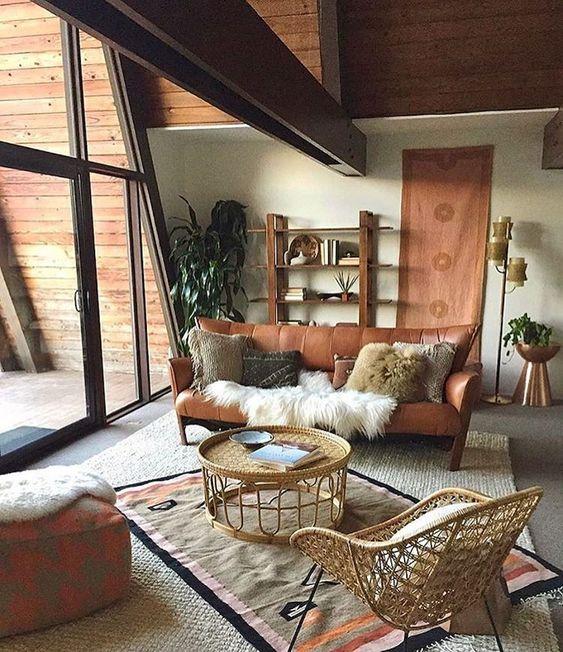 living room, grey floor, wooden wall, white wall, brown leaher sofa, rattan rug, ottoman, rattan coffee table, rattan chair