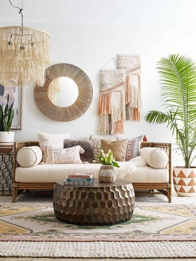 living room, petterned rug, white wall, macrame fringe accessories, rattan sofa with white cushion, brown round coffee table