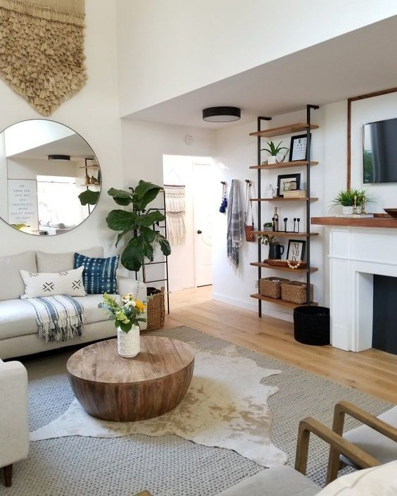 living room, white wall, white fireplace, wooden floor, grey rug, white sofa, round mirror, wall shelves,