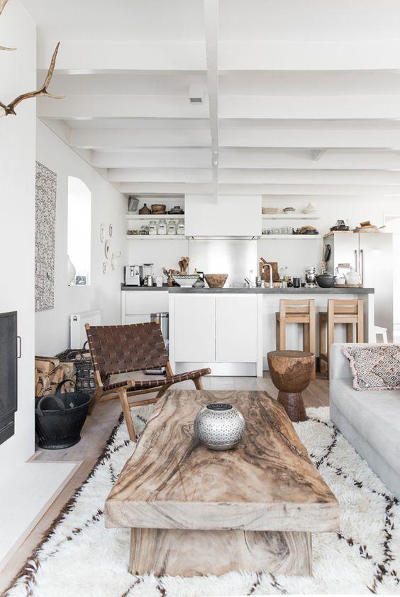 living room, white wall, white open kitchen, white sofa, white rugs, wooden coffee table