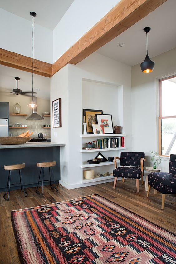 living room, wooden floor, patterned rug, white wall, blue kitchen, blue pattered chairs, floating shelves, black pendants