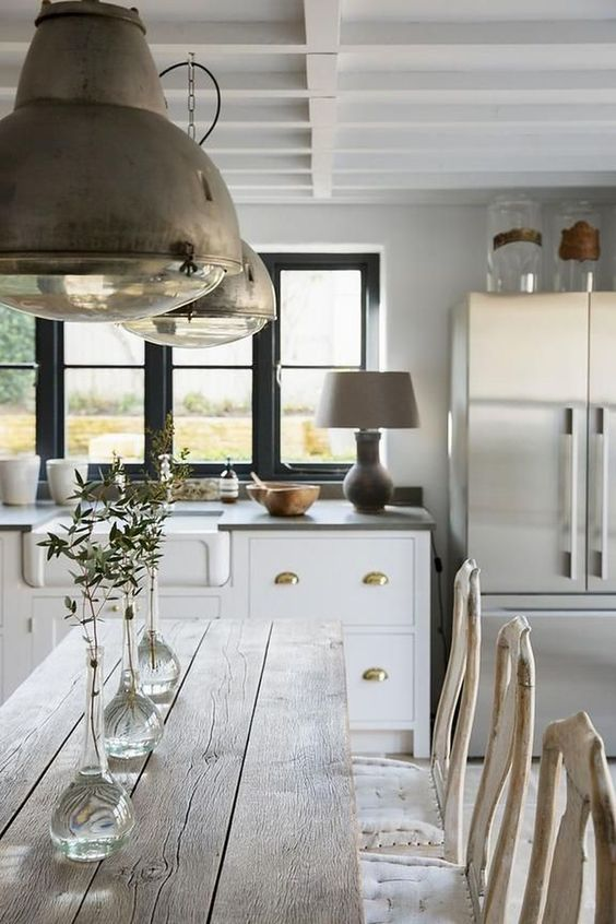 pale wooden table, white wooden chairs with white cushion, white wooden bottom cabinet, white wall, black framed windows, copper lamp, silver fridge