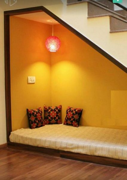 seats under the stairs, low wooden bench, white cushion, orange wall, red lamp, pillows