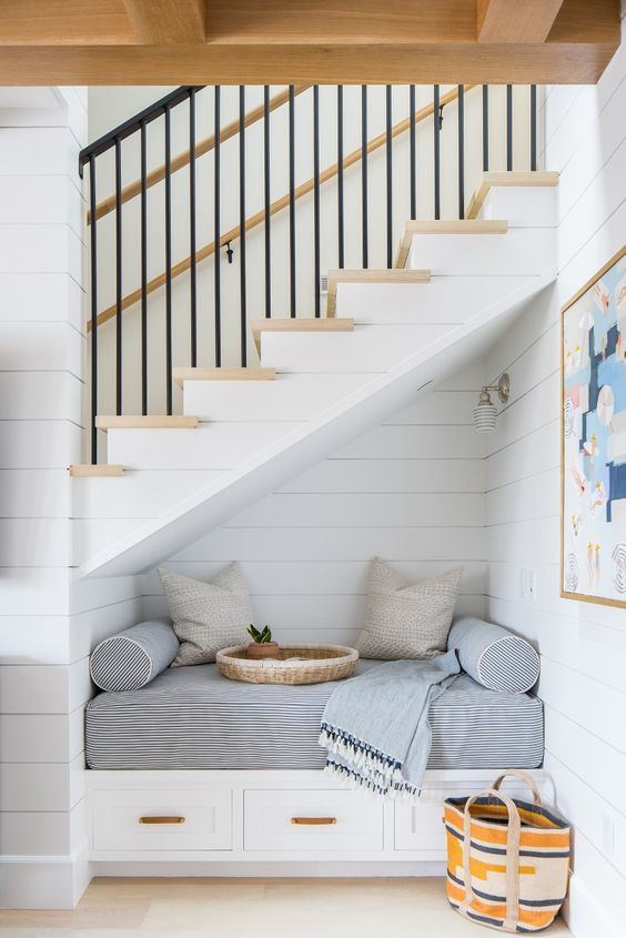 seats under the stairs, white plank wall, white sconce, white built in bench with drawers, striped cushion