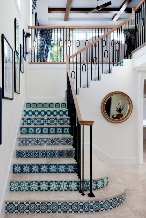 stairs with blue patterned tiles on vertical part, marble tiles, wooden rail with black metal suppor