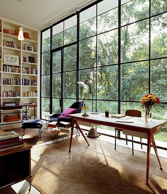 study, brown rug, white wall, large glass windows, tall white shelves, black lounge chair
